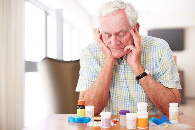senior-man-looking-at-medications