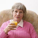 woman sitting drinking orange juice